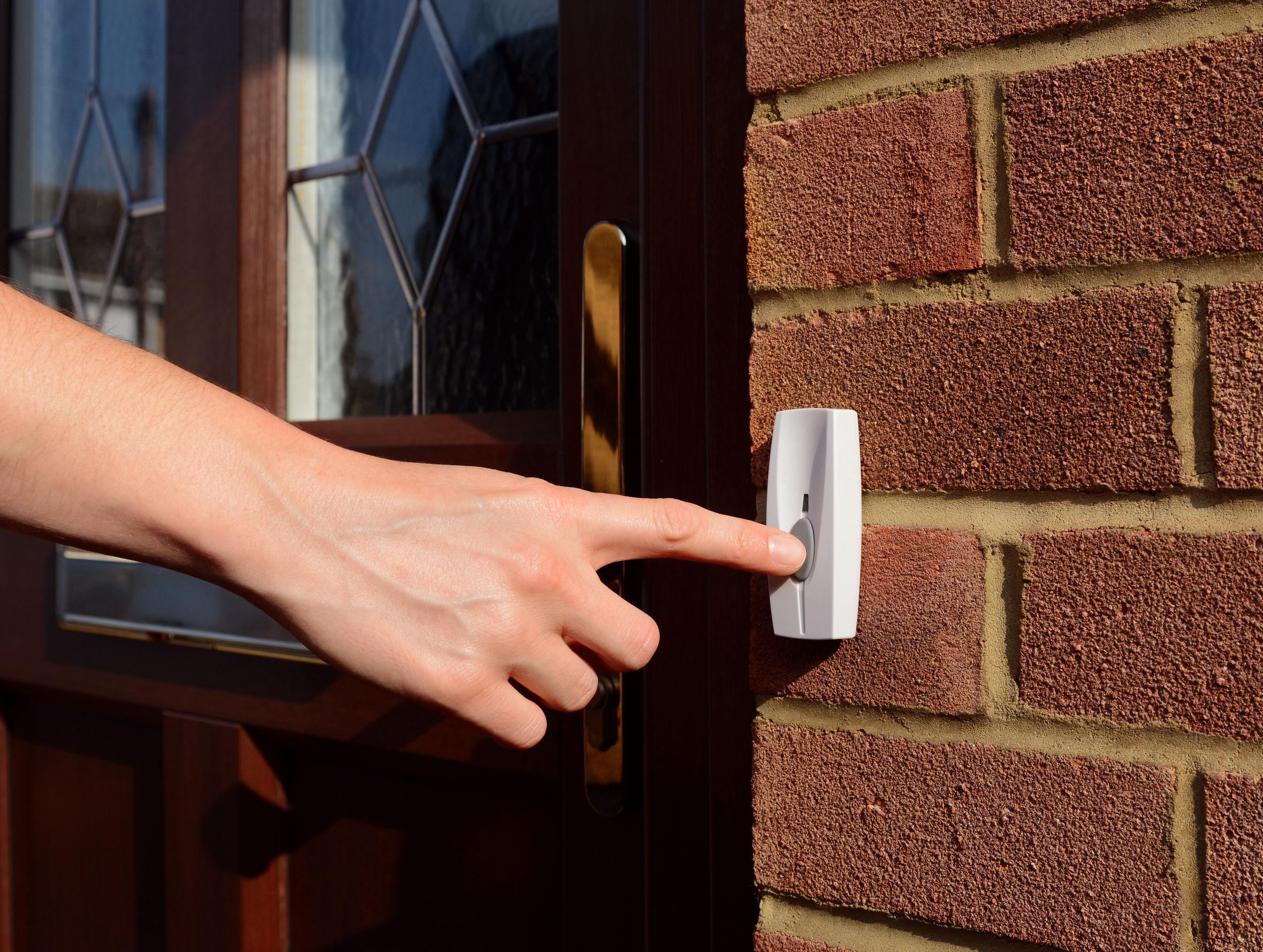 mujer se extiende su mano para que suene un timbre en la puerta principal de una casa
