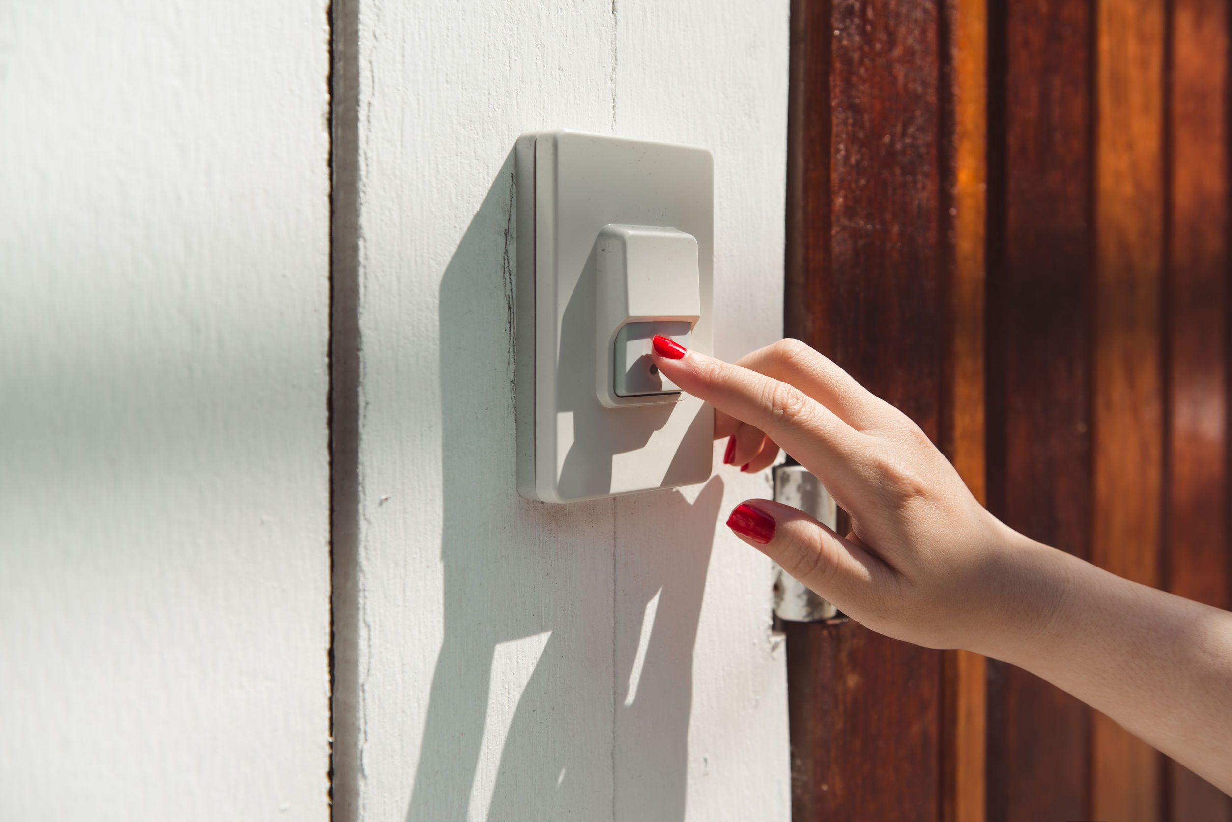 En la puerta de entrada, la mujer toca el timbre de la puerta