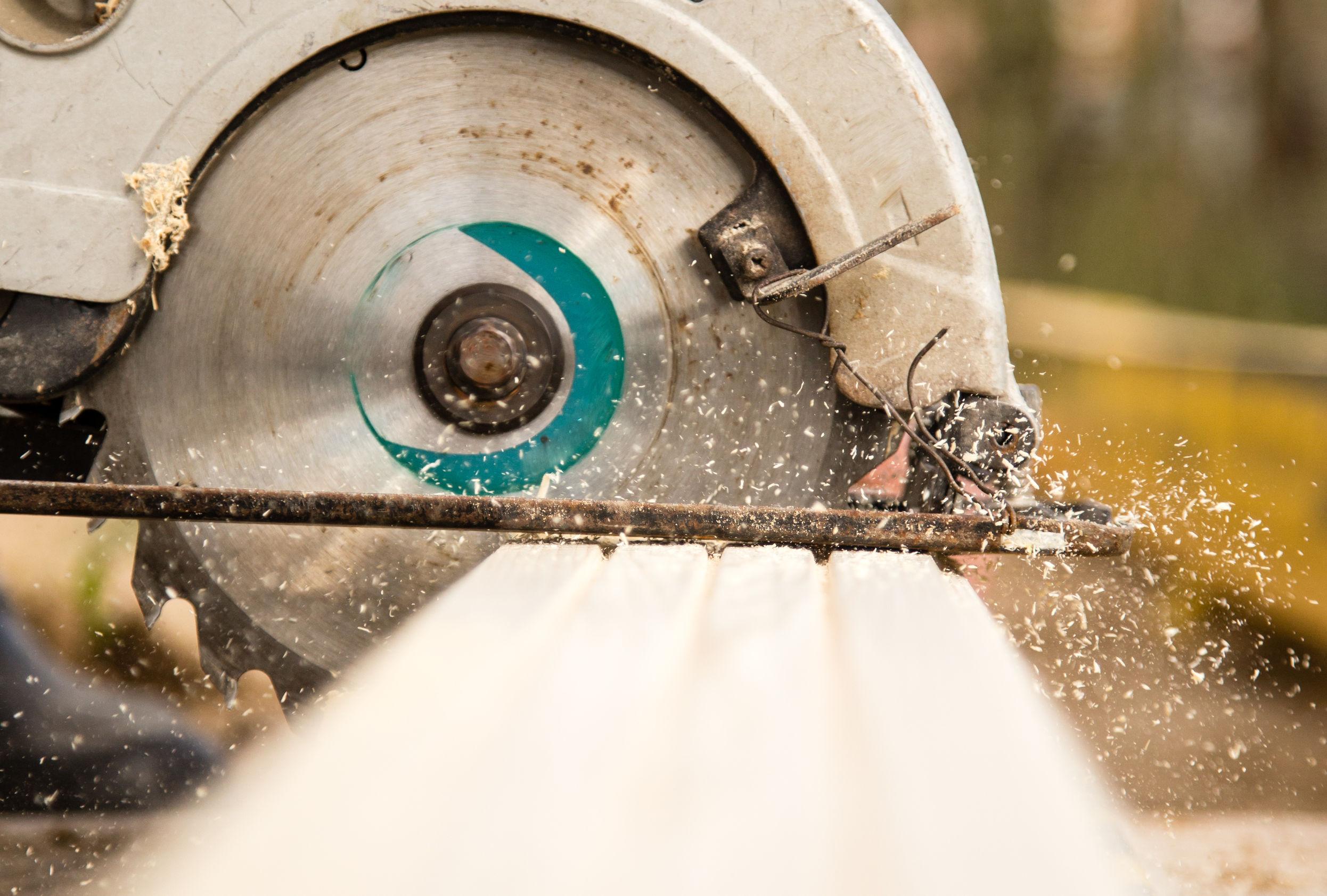Trabajador sierra un tablón de madera en un sitio de construcción.