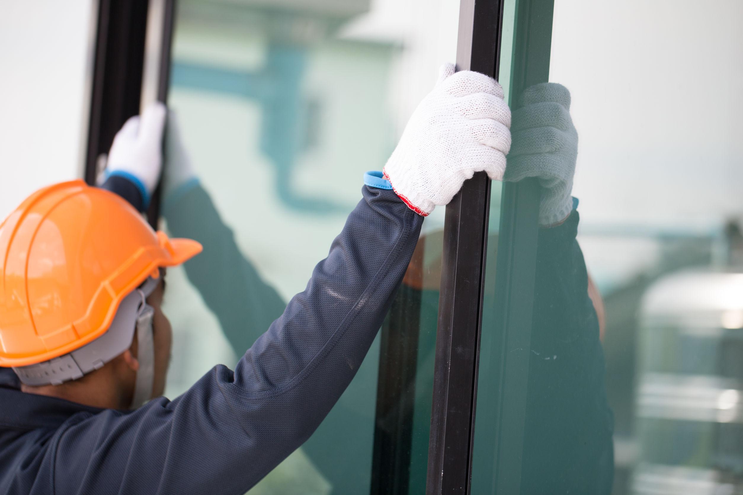 Las manos del técnico instalarán ventanas de aluminio