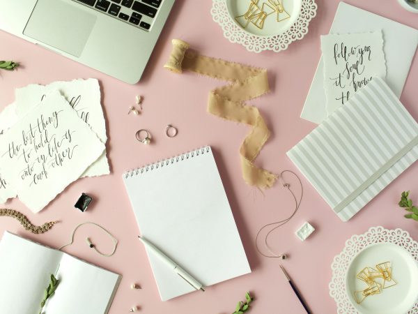 65012329 – flat lay, top view office table desk. feminine desk workspace with laptop, diary, spool with ribbon, calligraphy quotes and golden clips on pink background.