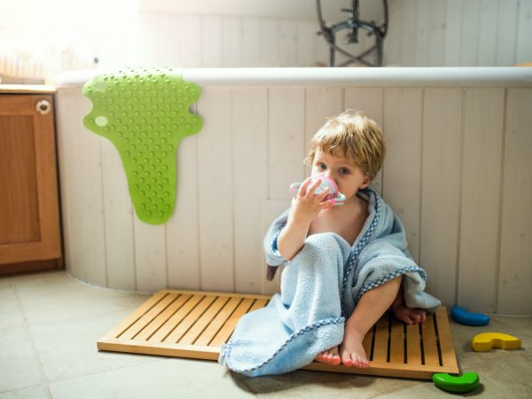 A toddler boy wrapped in towel sitting on the floor in the bathroom at home, drinking.