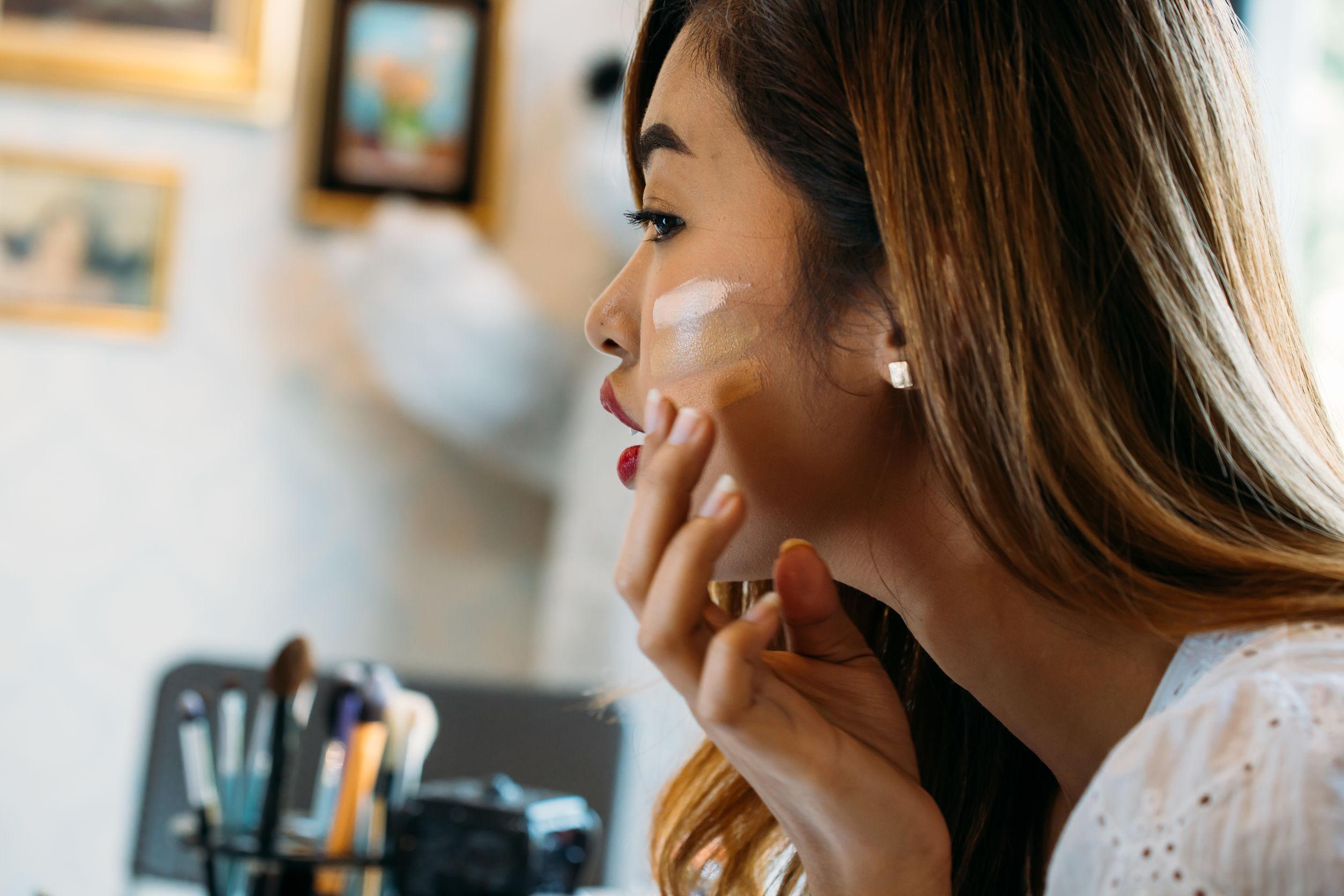 joven mujer asiática con labios rojos aplicando corrector en la cara sobre fondo borroso