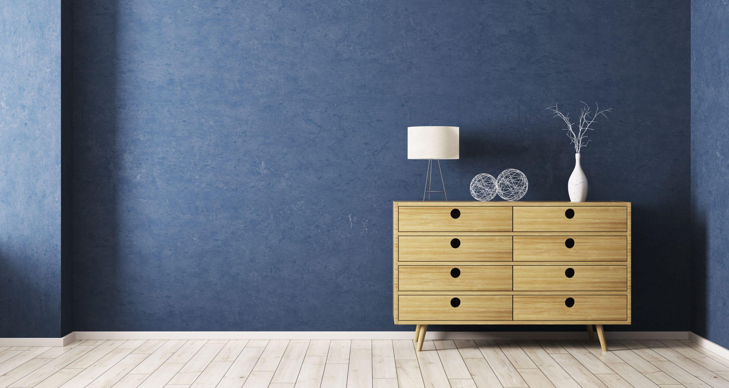 Comoda en habitacion con pared azul