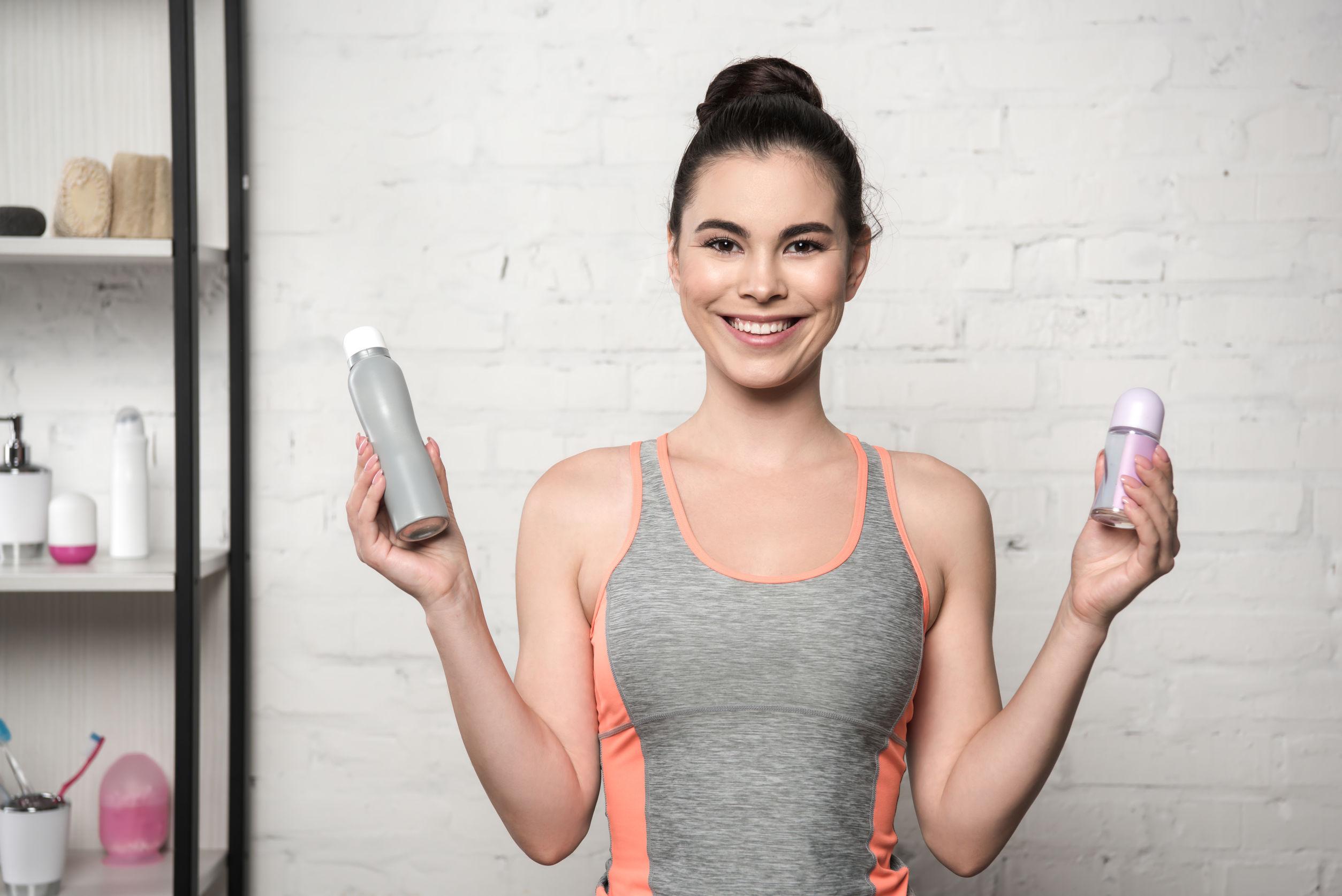 Mujer alegre sonriendo a la cámara mientras sostiene desodorantes