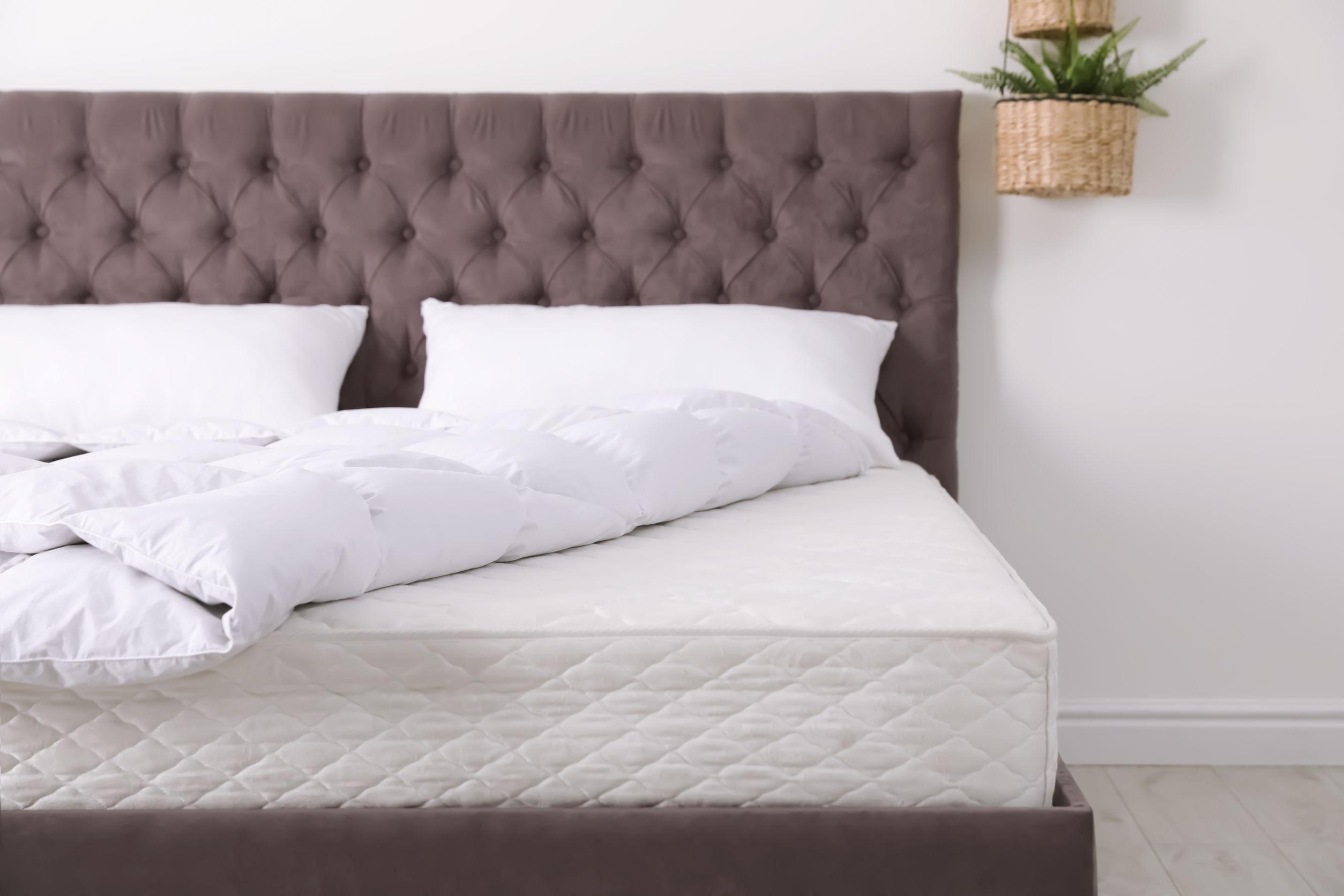 Cama cómoda con colchón nuevo en la habitación