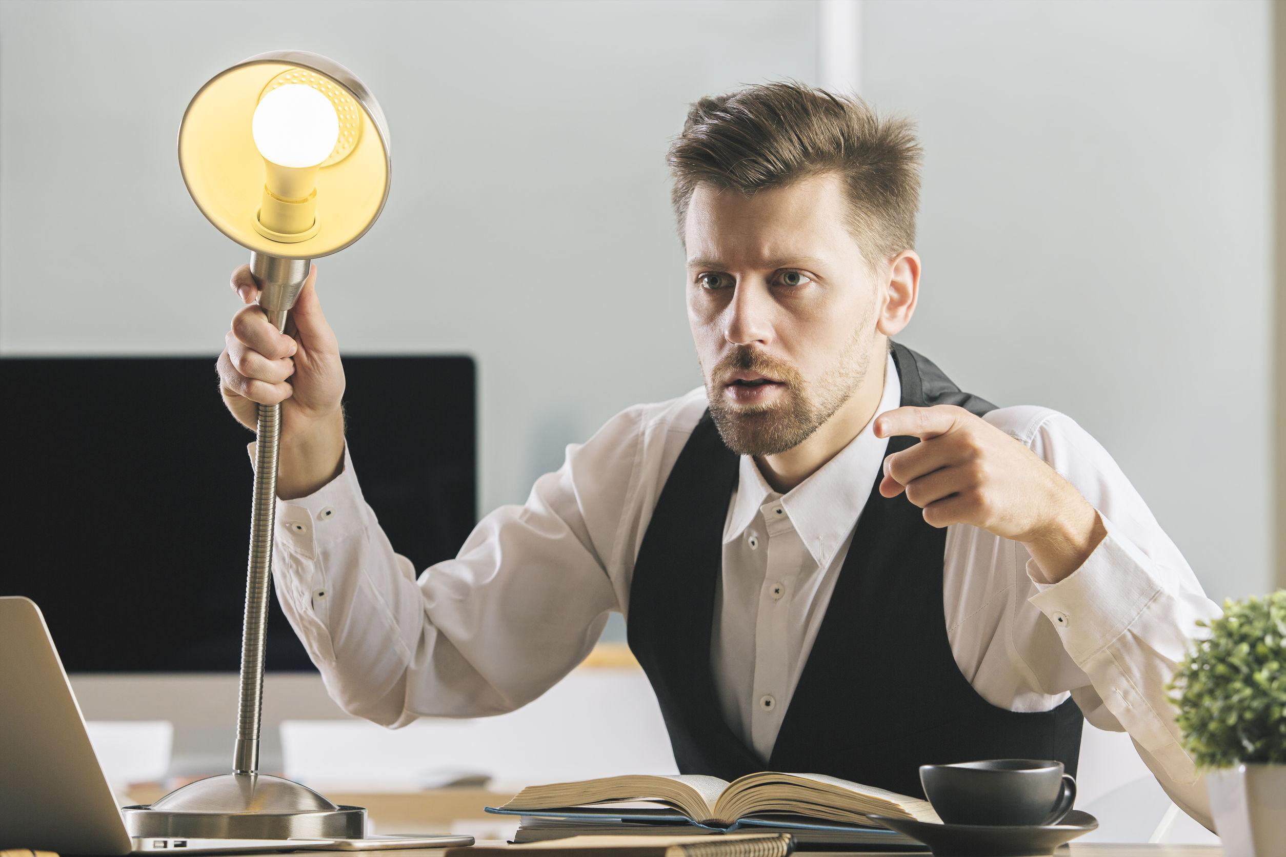 Hombre en escritorio sujetando lampara