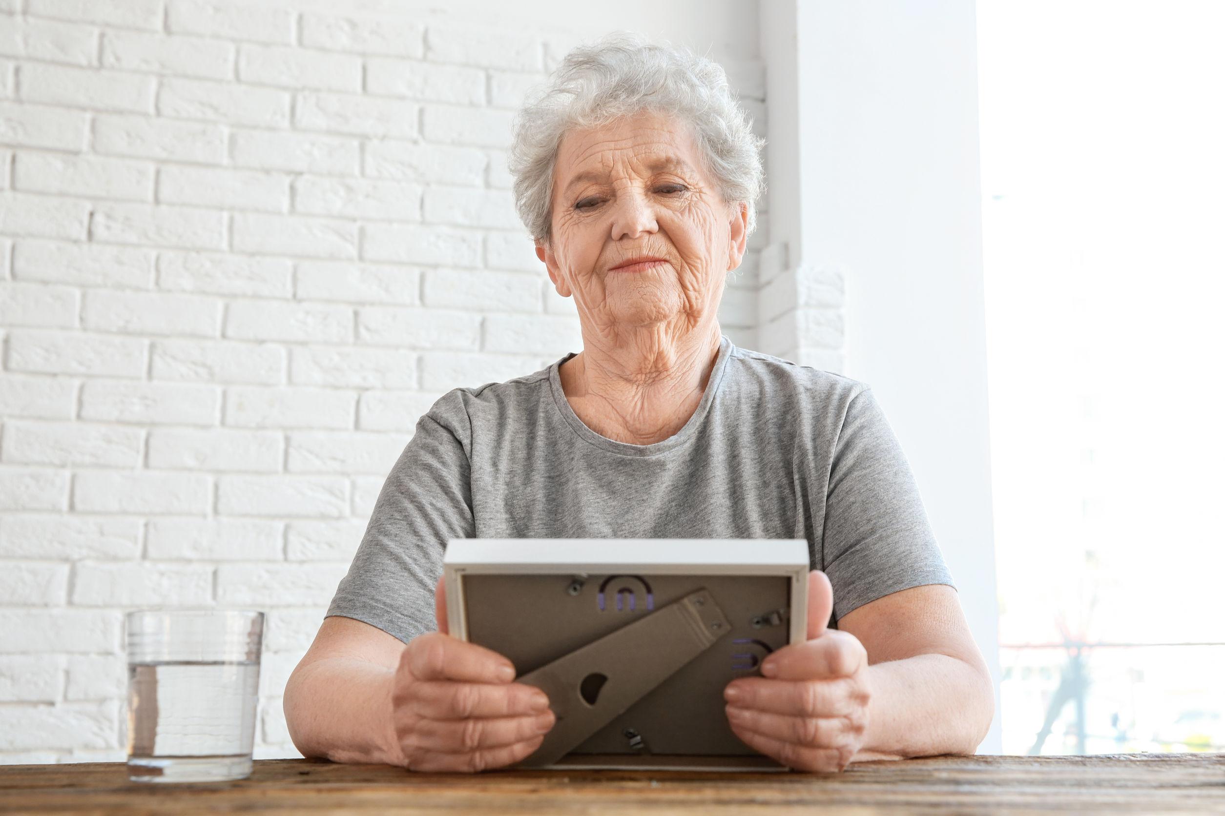 Mujer de la tercera edad sosteniendo un marco de fotos