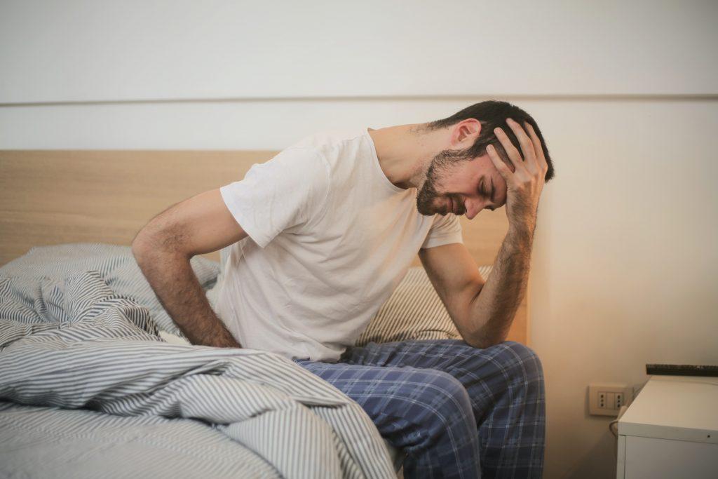 Hombre sentado en la cama con dolor de espalda