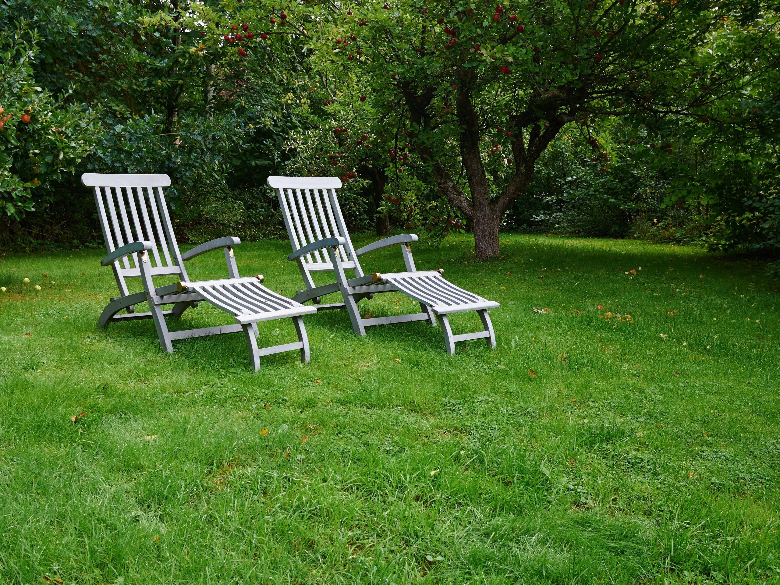 Relajantes cómodos sillones de madera de diseño clásico en el jardín con fondo de paisaje verde