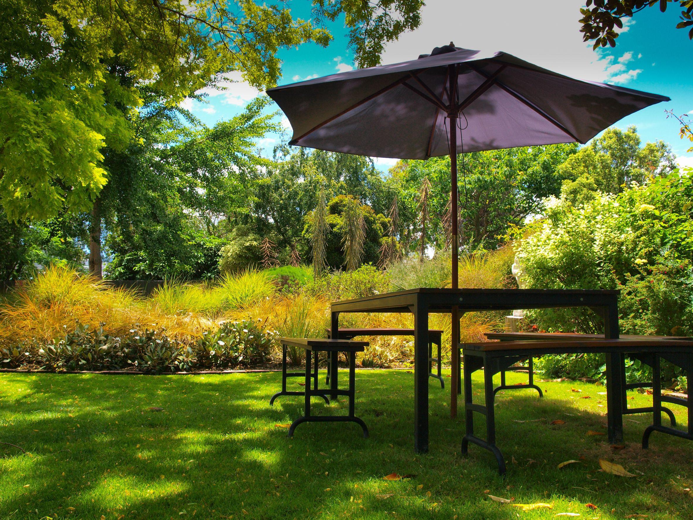 Mesa de comedor con sillas y sombrilla en la sombra de un frondoso jardín