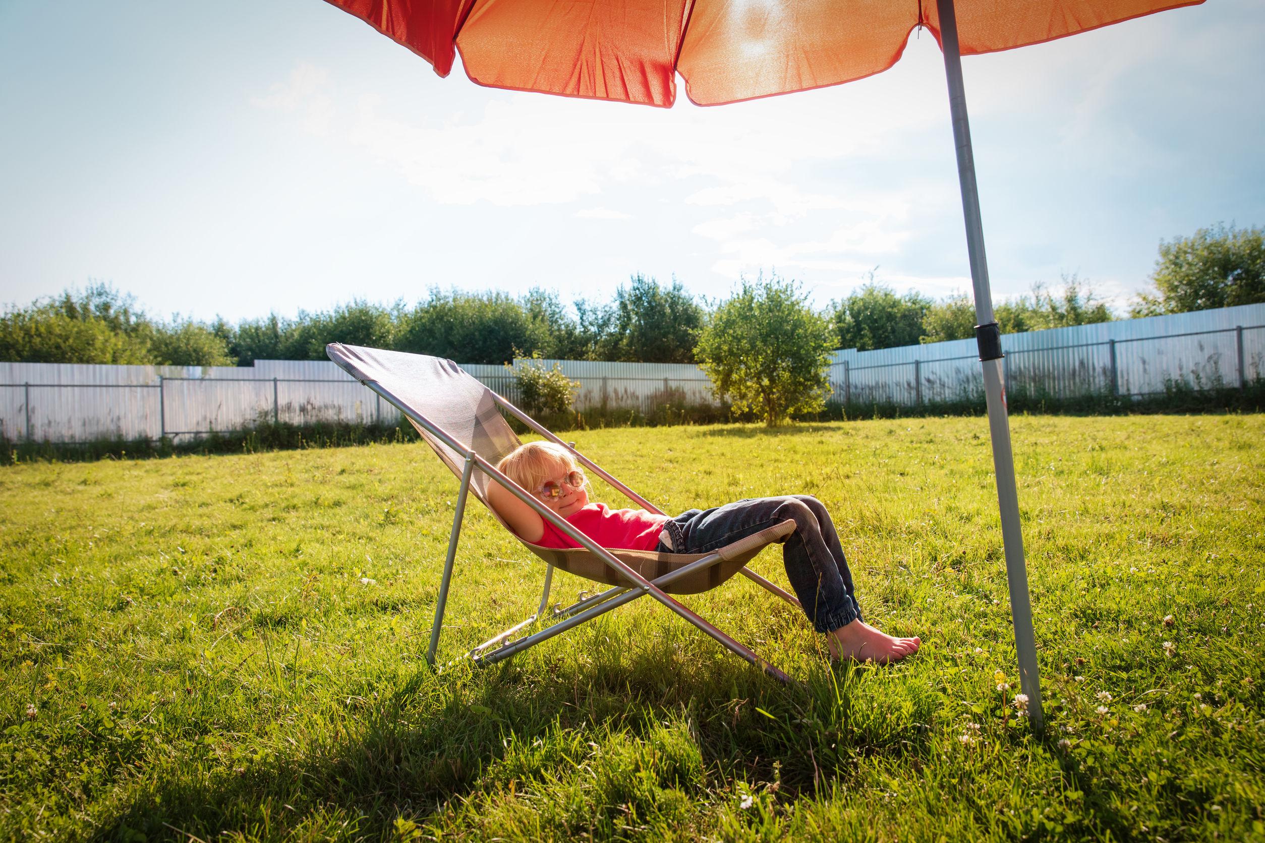 Niña en patio sentada bajo una sombrilla