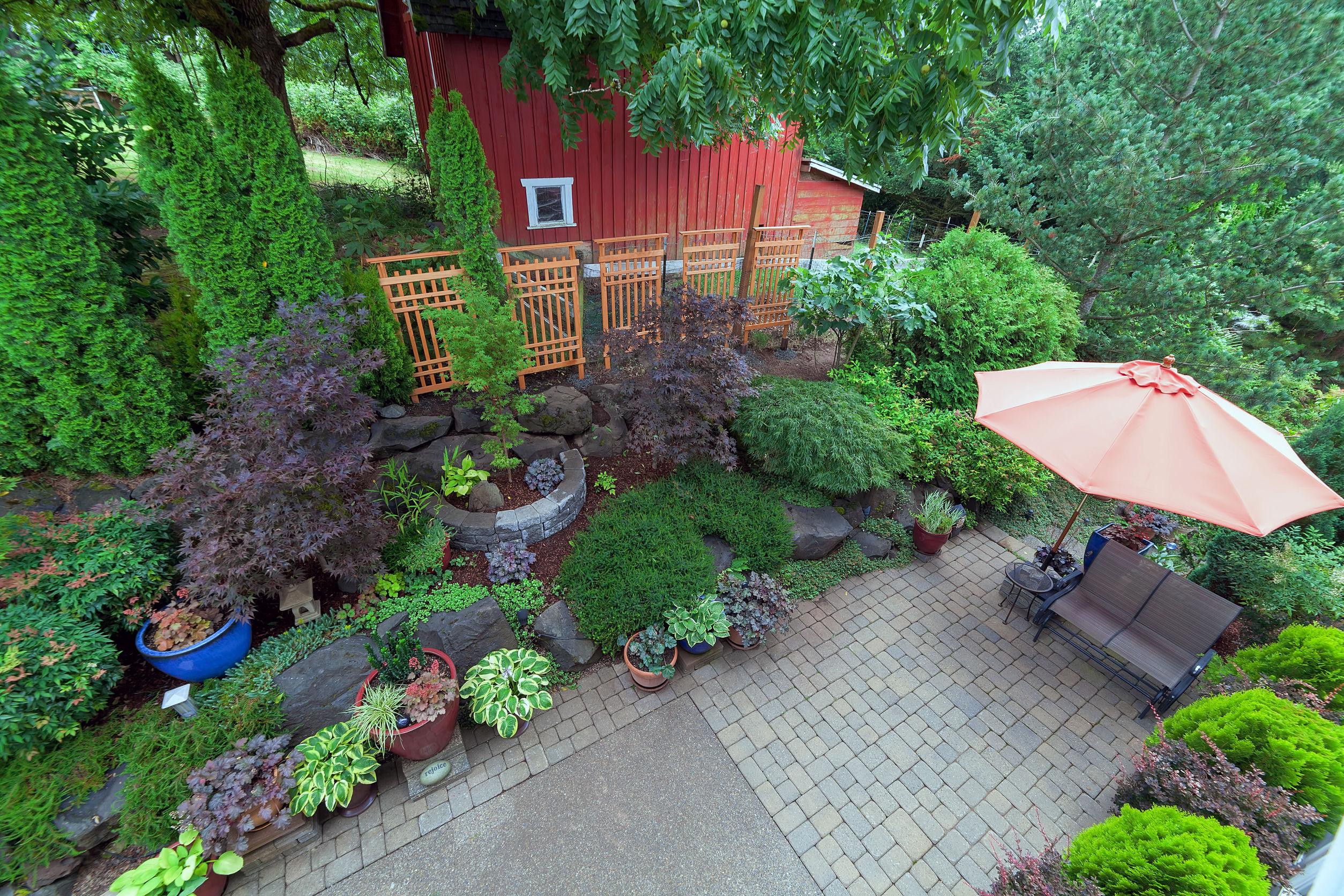 Patio trasero paisajismo jardín con mobiliario estanque árboles pavimentadas con ladrillos de adoquines del patio plantas en macetas arbustos y rocas granero rojo