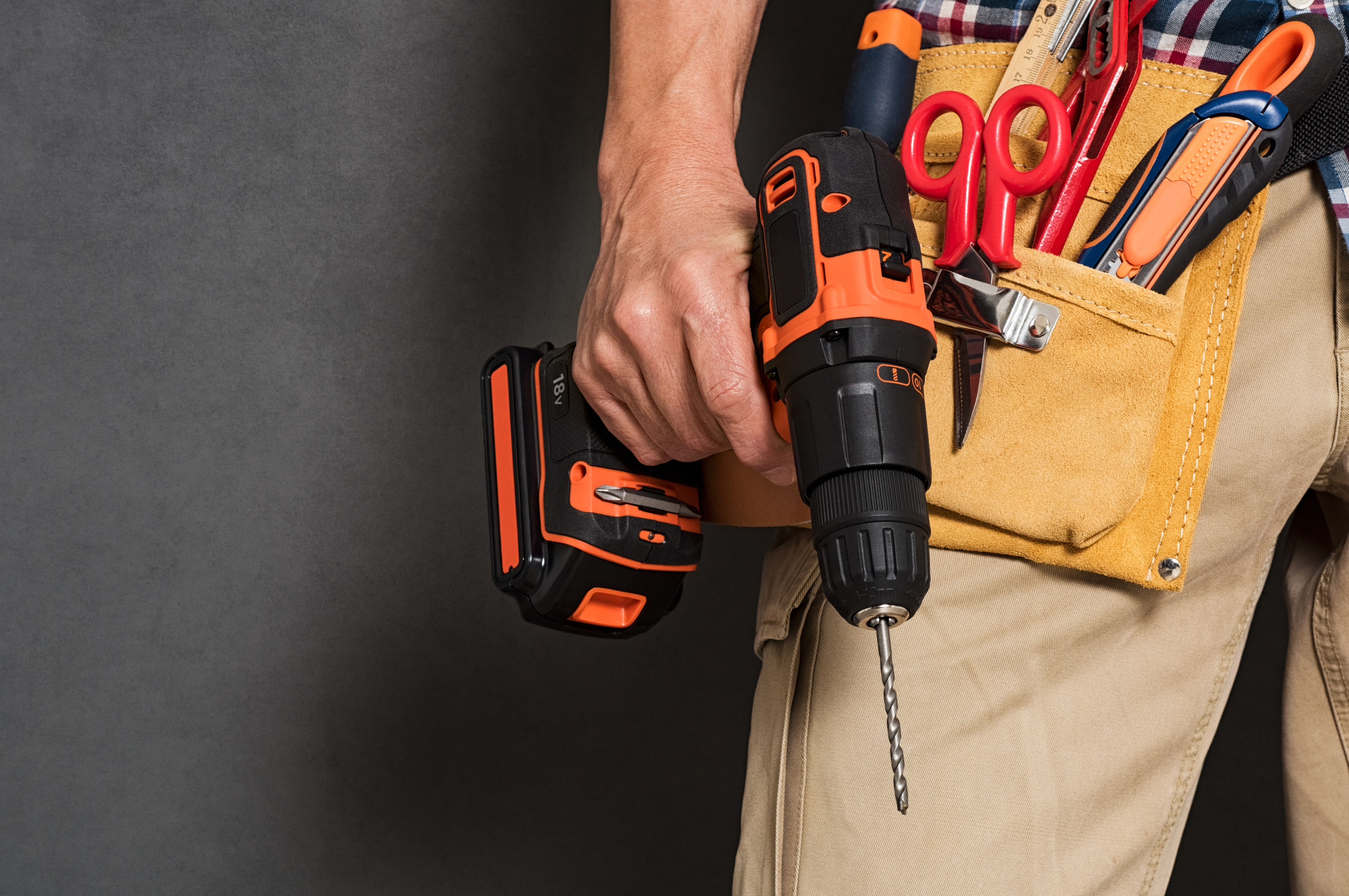 Hombre con cinturon de herramientas sostreniendo raladro