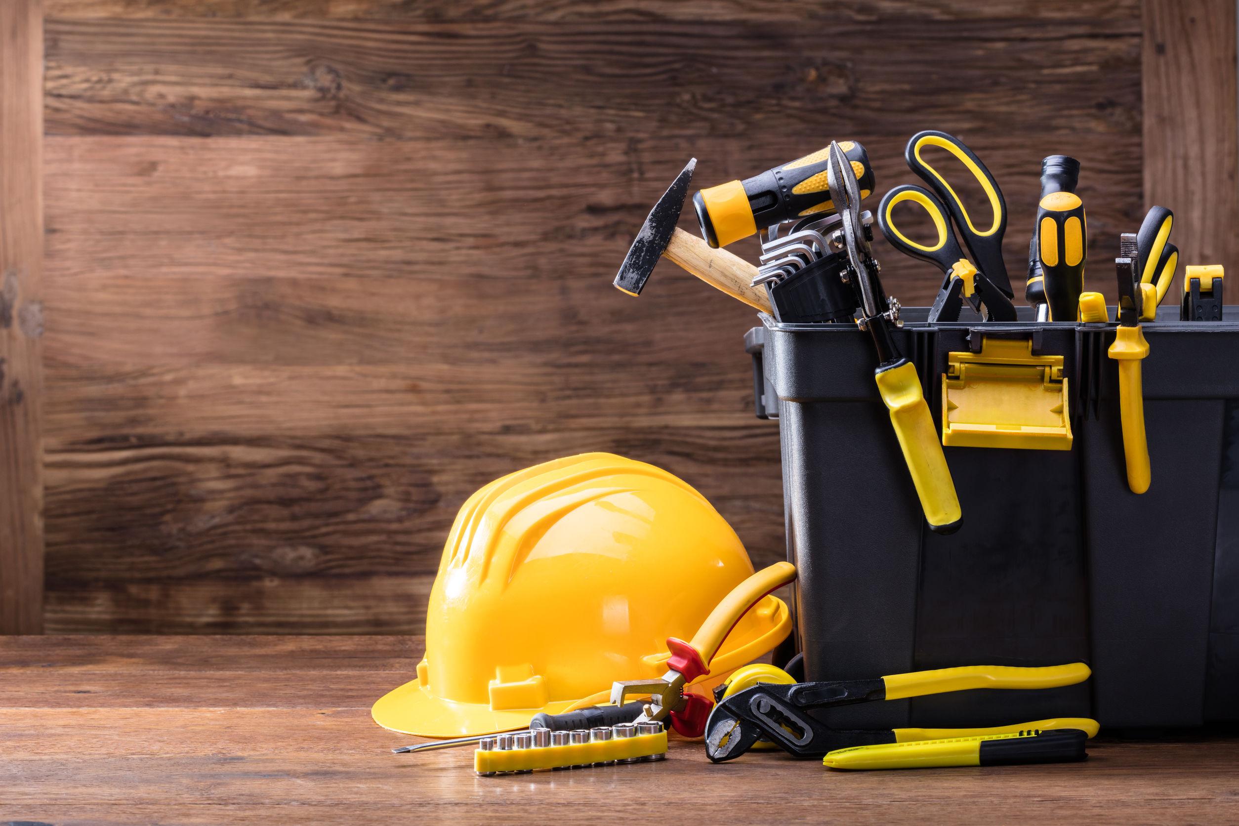 Close-up de casco de seguridad con herramientas en el contenedor negro sobre la mesa de madera