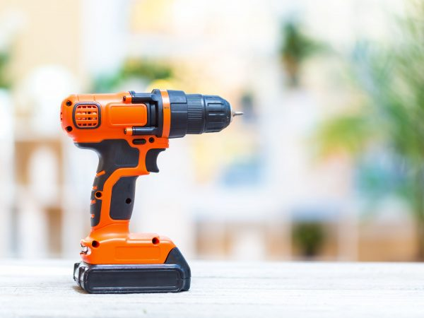Cordless electric drill on a bright interior room background
