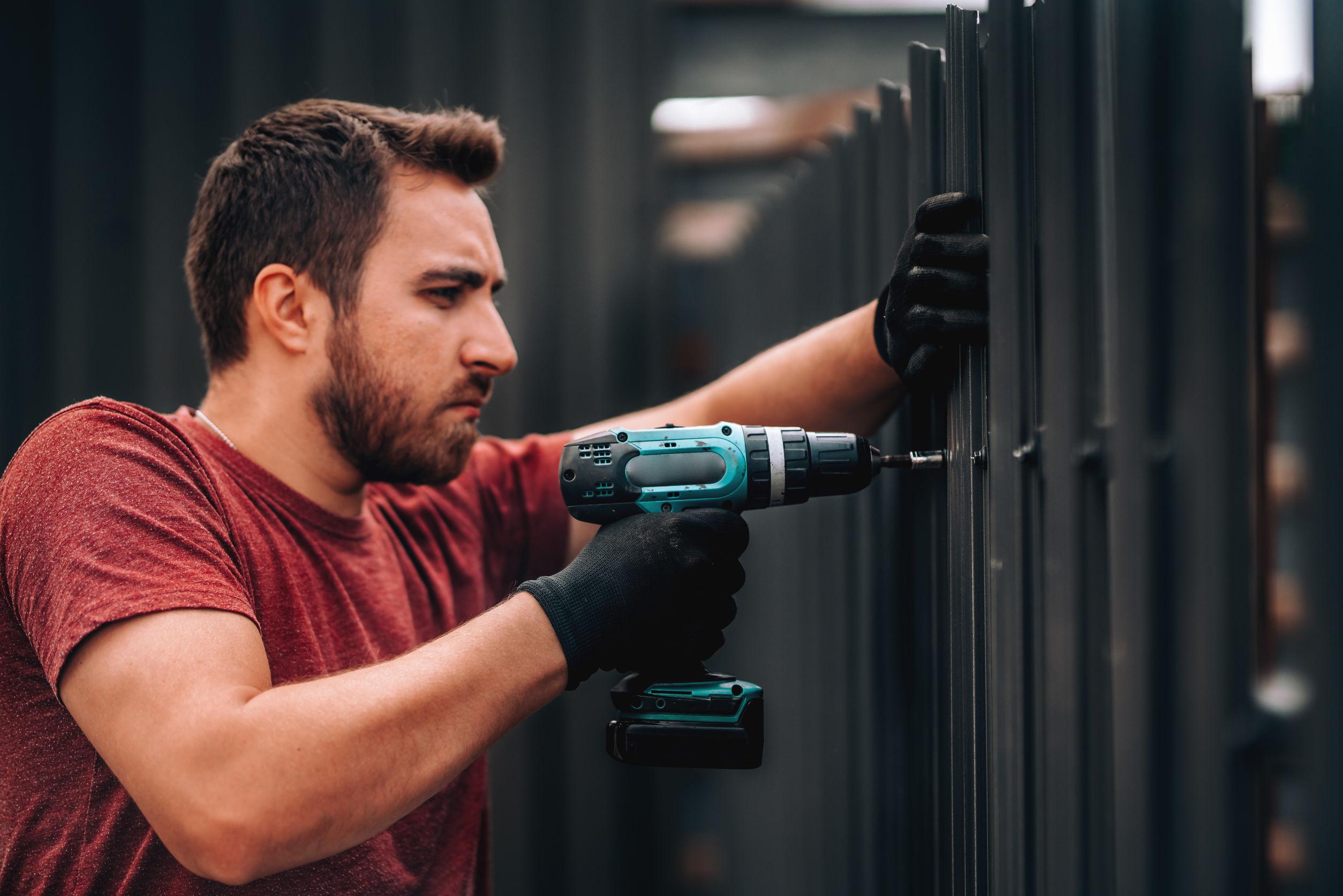trabajador de la construcción instalando elementos metálicos con taladro inalámbrico