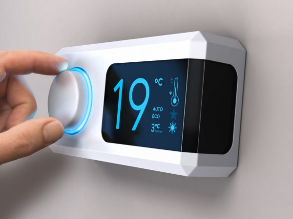 69321322 – hand turning a home thermostat knob to set temperature on energy saving mode. celsius units. entre composite image photography and has a 3d background.