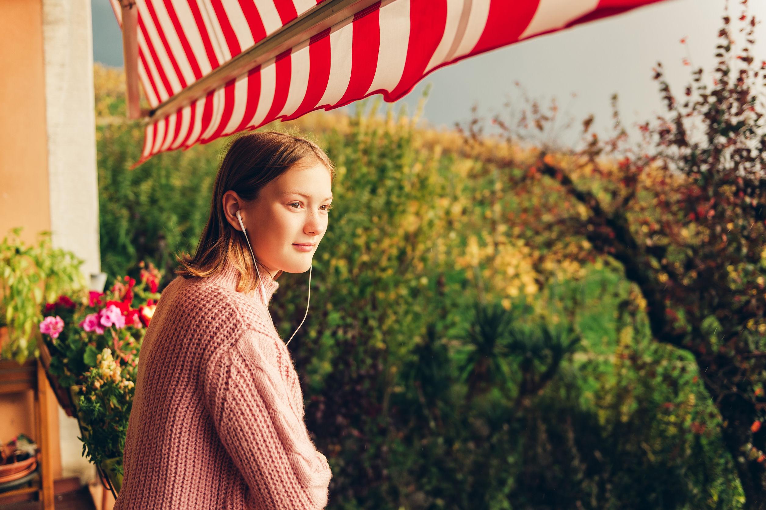 Hermosa adolescente disfrutando de una agradable y soleada tarde en el balcón con toldo
