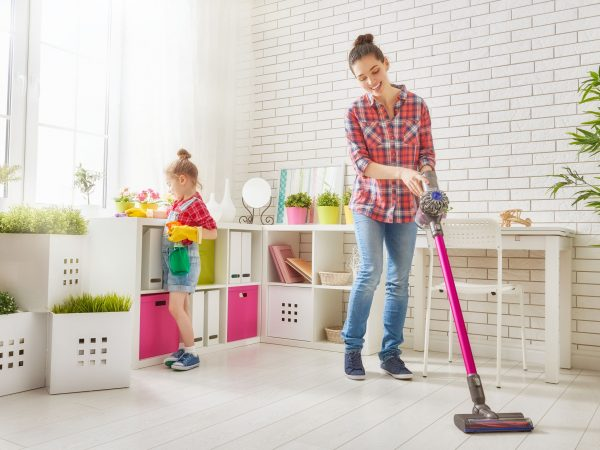 54018562 – happy family cleans the room. mother and daughter do the cleaning in the house. a young woman and a little child girl wiped the dust and vacuumed the floor.