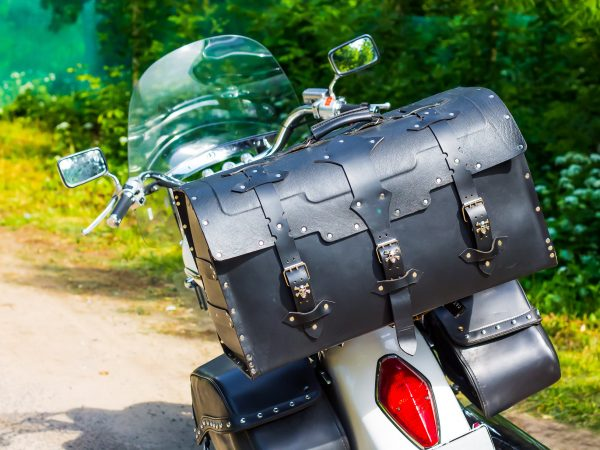 Leather motorcycle bag close-up. Travel by moto on a sunny summer day. Luggage system for motorcycles.