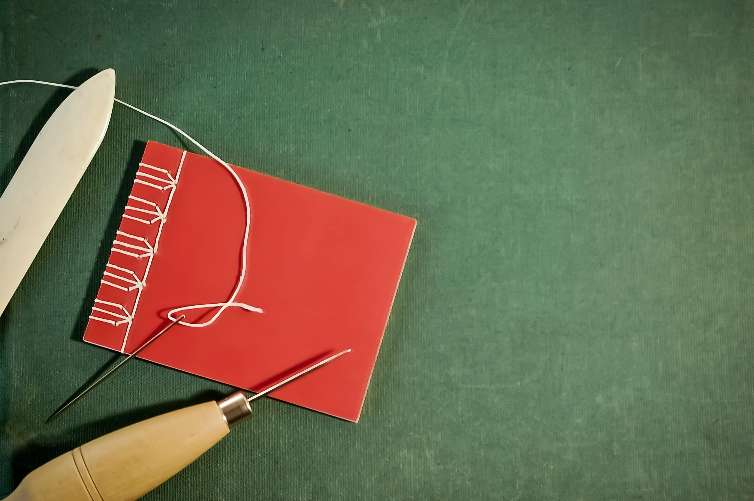 Cuaderno rojo cosido a mano con herramientas de encuadernación sobre fondo verde