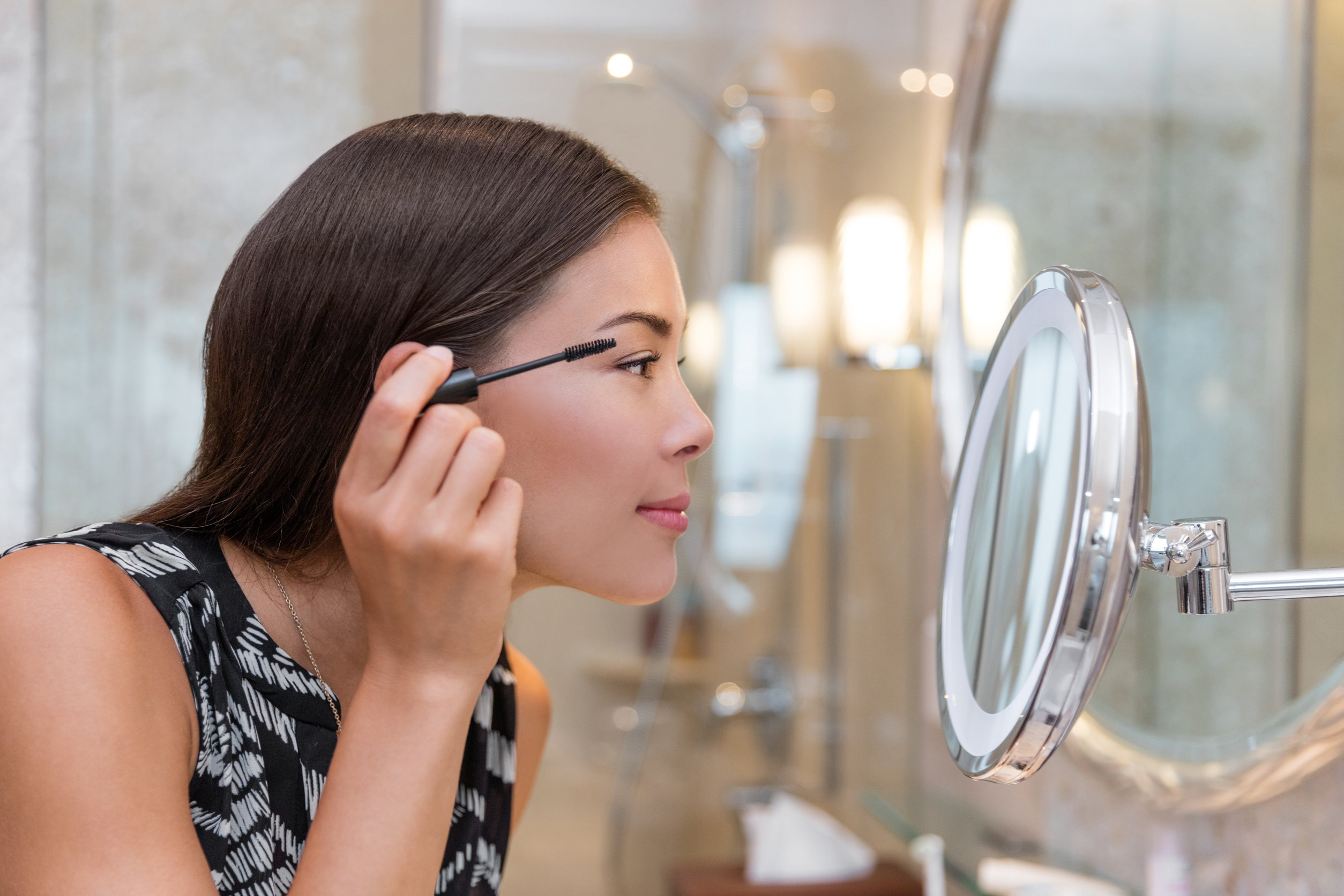 Mujer preparándose para el trabajo haciendo rutina de maquillaje matutino poniendo rímel en el espejo del baño en casa