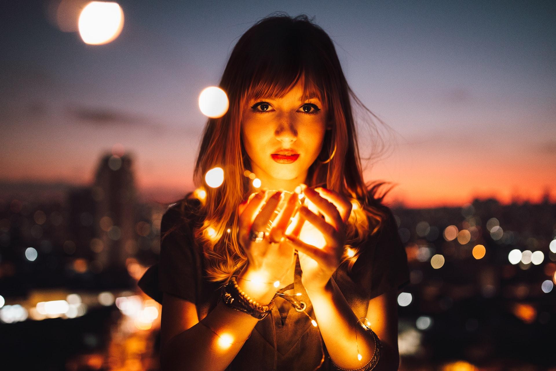 Mujer en atardecer con focos de luz