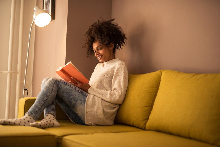 Jóven mujer leyendo un libro cómoda, disfrutando del Chaise Longue