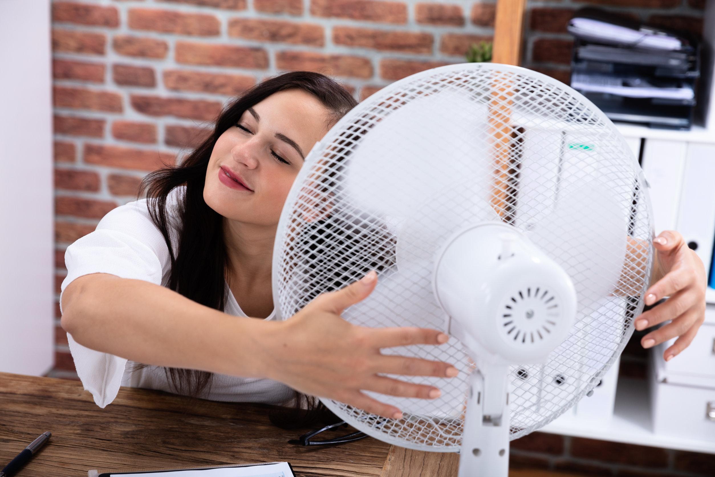Mujer tomando aire de ventilador