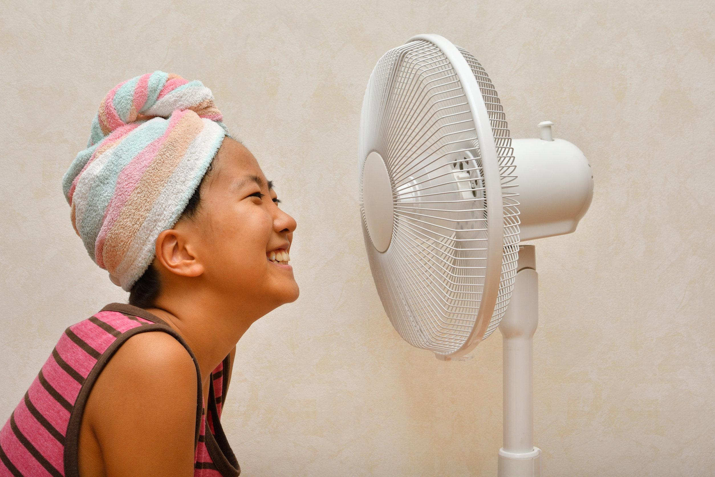 Niña sonriendo frente a ventilador