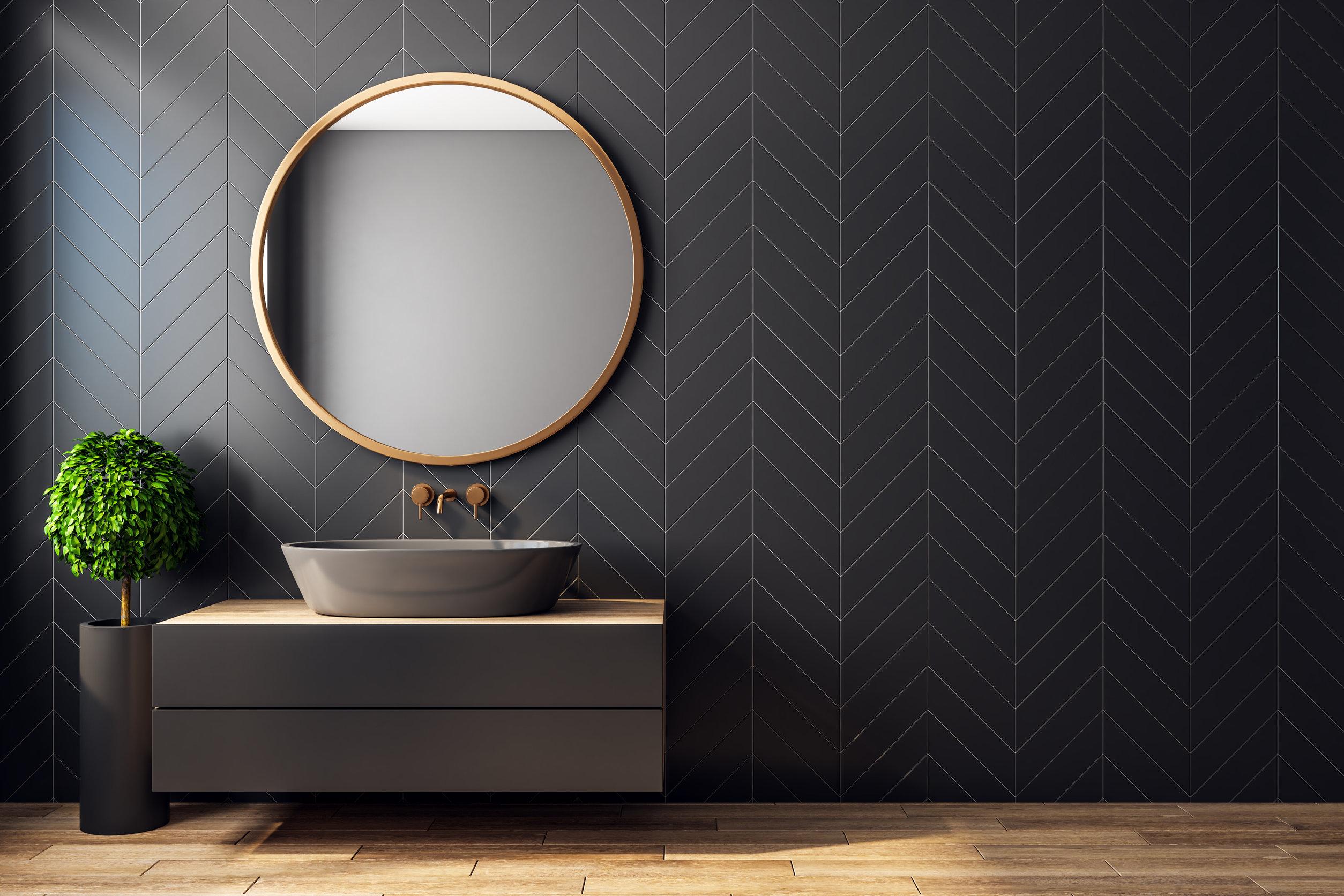 Interior de baño negro moderno con árbol decorativo, lavabo, espejo redondo, luz solar
