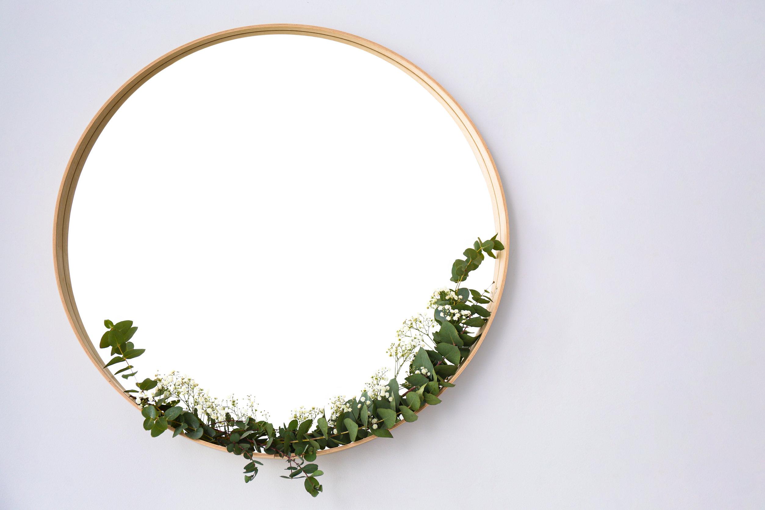 Nuevo espejo redondo en marco de madera sobre pared blanca, espacio para texto