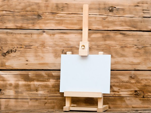 Wooden easel with clean paper on old wooden table