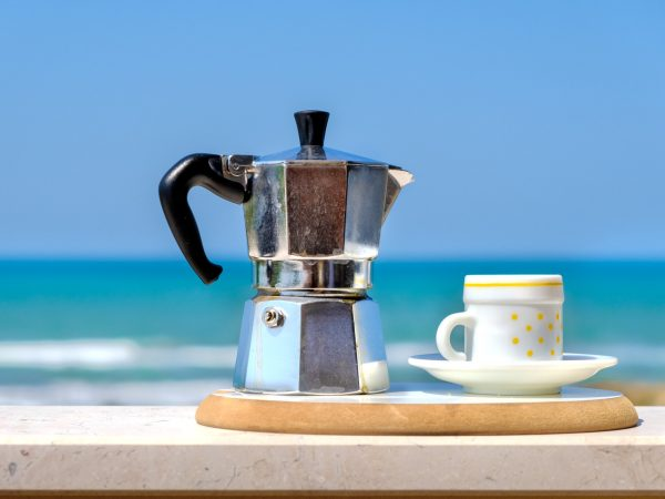 moka pot coffee maker sea background italian breakfast .
