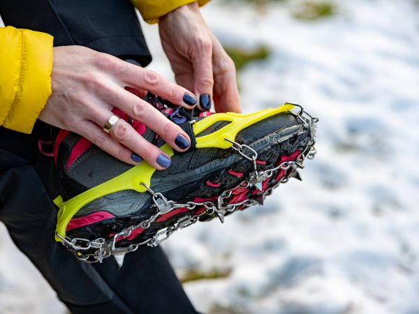 The mountaineer (girl with a manicure) puts on crampons.