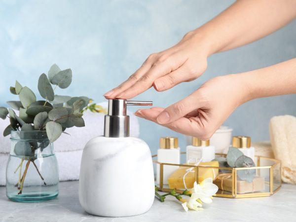 Woman using soap dispenser indoors, closeup view