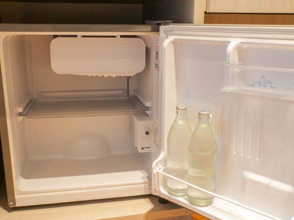 inside the mini fridge in hotel bedroom with fresh water bottle
