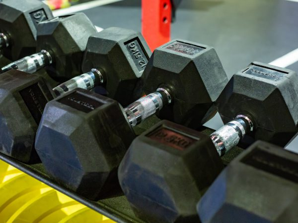 black rubber dumbbells. Hexagonal heavy duty weight set used for serious hardcore gym workouts, cross fit training and workout routines.