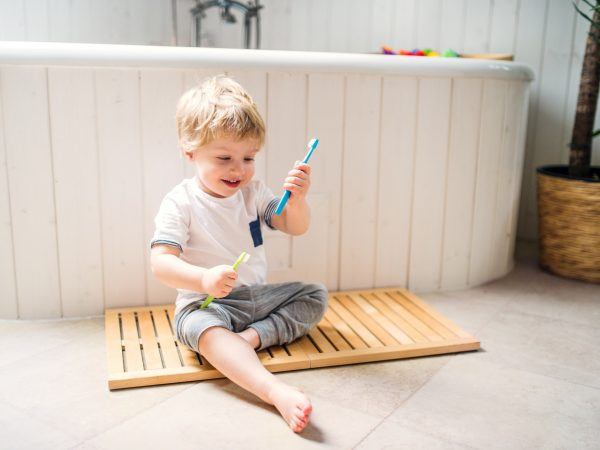 A happy toddler boy with a toothbrush sitting on the floor in the bathroom at home.