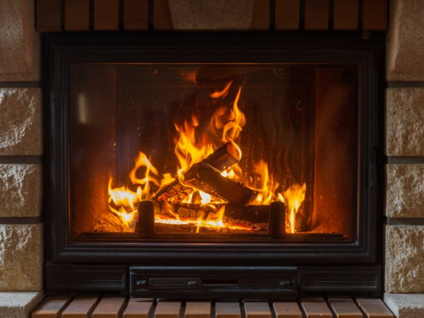 heating, warmth, fire and cosiness concept – close up of burning fireplace at home
