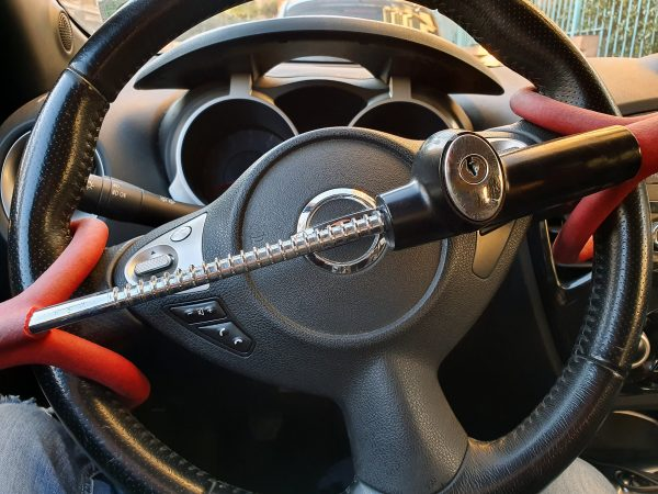 Anti-Theft Car Steering Wheel Lock Car Security. Black And Red Colors. Close Up View