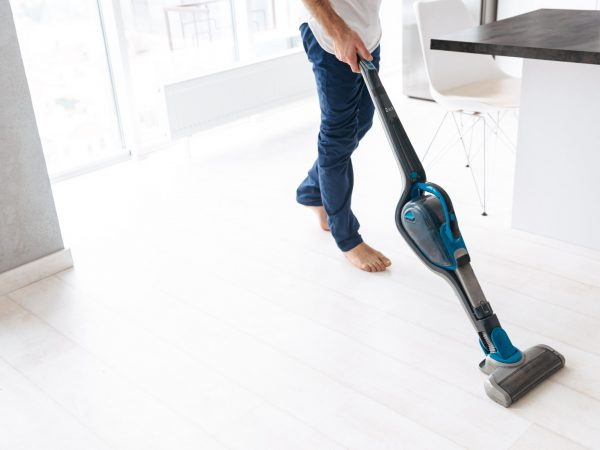 Close up of a man vacuuming the floor at the kitchen