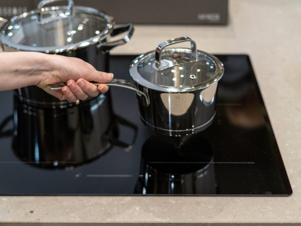 Women hand holding saucepan in modern kitchen over induction stove